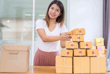 Jonge Aziatische meisje freelancer zakelijke particuliere werken thuis kantoor met laptop, notitie, koffie, verpakking sorteren box levering online markt op bestellingen tot klant. Stockfoto