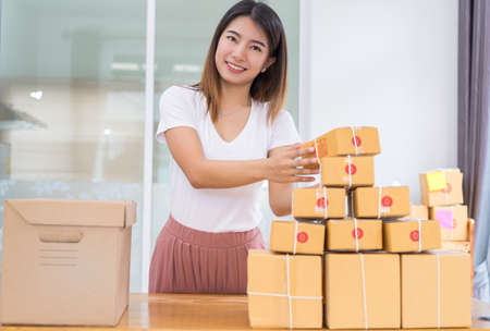 Privates Büro des zu Hause des jungen asiatischen Mädchenfreiberuflergeschäfts, das zu Hause mit Laptop, Anmerkung, Kaffee, verpackender Sortierkasten-Lieferungson-line-Markt auf Kaufaufträgen zum Kunden arbeitet. Standard-Bild - 85045972