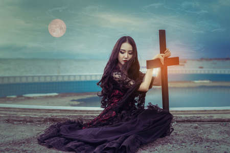 Witch or vampire beautiful woman sitting and holding cross the ghost with  screaming darkness and nightmare, horror of scary fear on hell in halloween festival, and blood moon refurbished by NASA Stock Photo