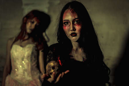 diabolic: Witch death the ghost holding skull and zombie in dress women with blood skin is screaming darkness and nightmare background, horror of scary fear on hell is monster devil girl in halloween festival concept
