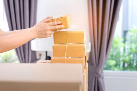 Close-uphanden die de levering van de sortendoos online markt op aankooporders houden aan klant in bureau.