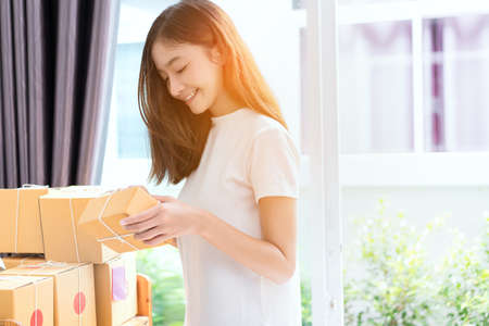 delivery service: Young asian girl freelancer business owner working at home office with note, post it, packaging sort box delivery online market on purchase orders to customer.