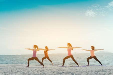 젊은 그룹 여성 요가 연습 포즈와 클래스 운동에 매트 휴식 해변과 해변에서 건강을 위해 피트 니스 스포츠 일출 현대 도시