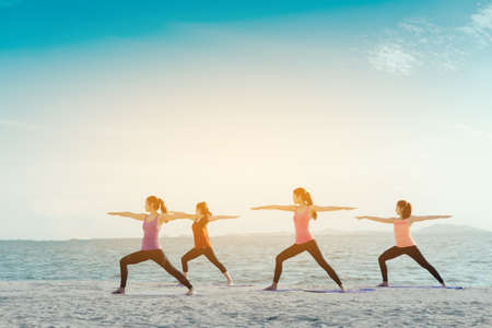 Young group women yoga practice on mat relaxation in class exercise with pose fitness sport for healthy on the beach and seaside  modern city at sunrise relax Zdjęcie Seryjne