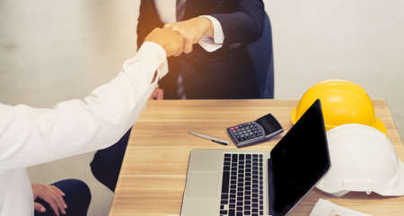 trusted: Giving fist bump hands of businessmen together teamwork partner and join group successul project with laptop, calculator, pen, safety helmet Stock Photo
