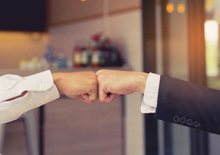 trusted: Closeup, Giving fist bump hands of businessmen together teamwork partner and join group successul project