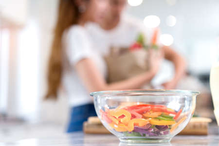 Closeup bowl, Young Asian man and woman couple together cutting slice vegetables making each salad and food for dinner menu with fruits in kitchen room and home romantic indoor sweet, happy Stock Photo