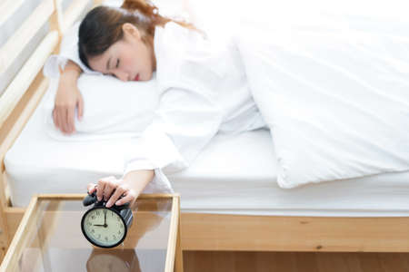 Young asian woman press the button snooze wake up alarm clock alert in the morning and sleeping lazy next on bedroom at home Stock Photo