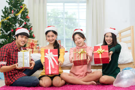 Young Asian group man and women together teenager friend with santa hat holding gift box surprise christmas holidays and  christmas tree background in room at home relaxing celebrating new year