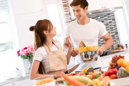 Young asian woman cutting slice vegetables making salad healthy food with fruits and man cooking menu for dinner in kitchen at home couple together romantic Zdjęcie Seryjne