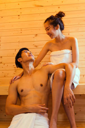 Young asian man and woman couple together sitting in sauna spa room with hot warm steam happy relaxing, resting for health care and skin in holiday at cabin