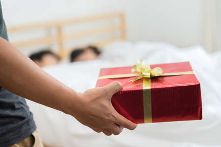 Closeup red gift box surprise, but Wife woman or girlfriend having an affair with a married man sleeping on the bed under pillow at home  Stock fotó