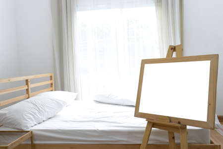 windows frame: Blank board white frame on wooden standing for poster in bedroom interior with window and pillow