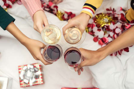 christmas backgrounds: Closeup hands holding glass of wine, cocktail, champagne friend drinking celebration christmas at home party interior on bed and box