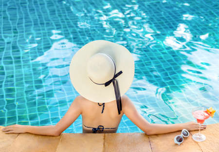 Bikini woman in pool relaxing with cocktail sunglasses, young asian beautiful sexy female resting in vacation on summer season with hat at resort swiming pool Banco de Imagens
