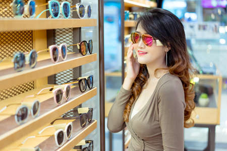 Beautiful young asian woman shopping sunglasses fashion with uv protection in optical shop market