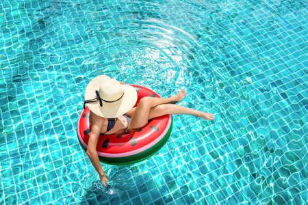 Woman bikini swimming pool on watermelon rubber ring relaxing vacation enjoying on summer season, Top view. Stock Photo