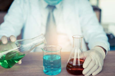 Scientist man with glasses working chemistry mix research and conducts experiments by synthesis compounds in laboratory and the test tube, lecture results