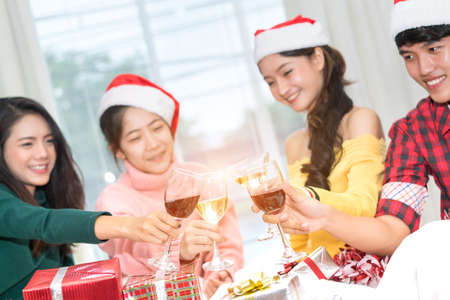 Christmas home party cocktail clink concept, Young asian group holding glass of wine, champagne friend drinking celebration interior