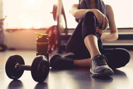 Exercice physique de femme dans la salle de sport remise en forme en train de se détendre, détenant des fruits pomme après un entraînement sportif avec haltère et protéine shake bouteille bodybuilding mode de vie sain Banque d'images