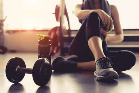 Frauenübungstraining im Turnhalleneignungsbrechen entspannen sich, Apfelfrucht halten, nachdem Sport mit dem gesunden Lebensstil Bodybuilding der Dummkopf- und Proteinrüschebox gestreift worden ist. Standard-Bild