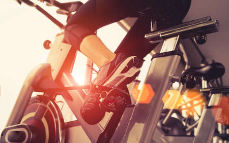 Exercice d'entraînement cardio-vélo au gymnase de remise en forme d'une femme prenant une perte de poids avec une machine aérobie pour une silhouette saine et mince le matin Banque d'images