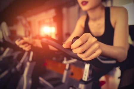 아침에 슬림하고 단단한 건강을 위해 에어로빅으로 체중 감량을받는 여성의 피트니스 체육관에서 운동 자전거 운동을하십시오.