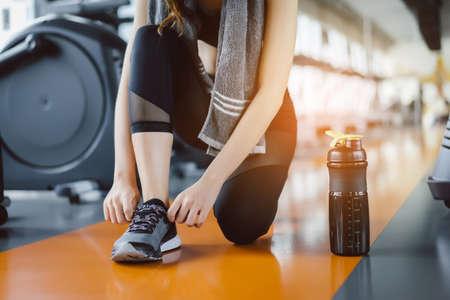 El asiático de la chica joven se arrodilló para hacer encima de sus cordones con batido de la proteína en el gimnasio de la aptitud después de correr el entrenamiento del ejercicio para la construcción del músculo y del cardiovascular. Foto de archivo - 89842507