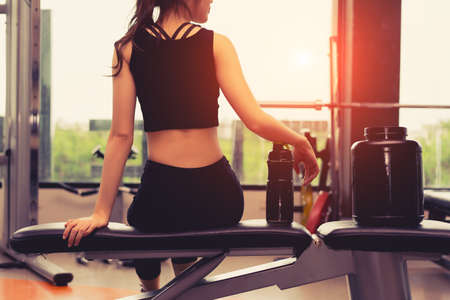 Woman exercise workout in gym fitness breaking relax holding protein shake bottle after training sport with dumbbell and healthy lifestyle bodybuilding. Banque d'images