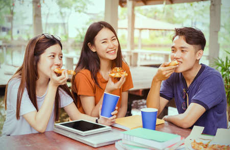 Students asian group together eating pizza in breaking time early next study class having fun and enjoy party italian food slice with cheese delicious at university outdoor