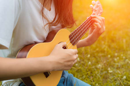 Closeup of girl playing ukulele in garden with acoustic guitar, young woman play music lifestyle classic