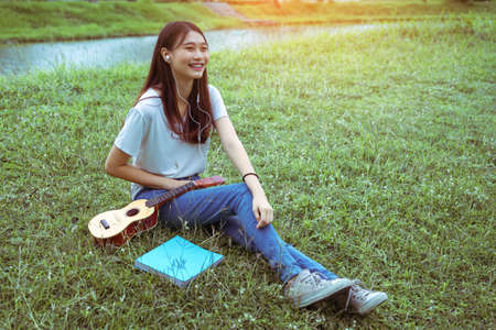 Young asian woman listening music and playing ukulele in garden acoustic guitar, young woman play music lifestyle classic