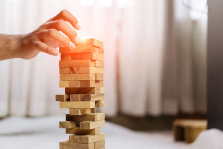 Hand of pulling wooden block before fail on building tower at home and drape change, choice business risking dangerous project plan failure construction