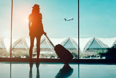 De reis van de silhouetvrouw met bagage die zonder venster luchthaven eind internationale bekijken of meisjestiener die in de koffer en de rugzak van de de ontspanningsholding van de vakantiezomer reizen