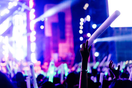 Crowd of hands up glow stick concert stage lights and people fan audience silhouette raising hands in the music festival rear view with spotlight glowing effect