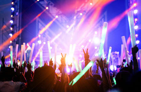 Crowd of hands up concert stage lights and people fan audience silhouette raising hands or glow stick holding in the music festival rear view with spotlight glowing effect