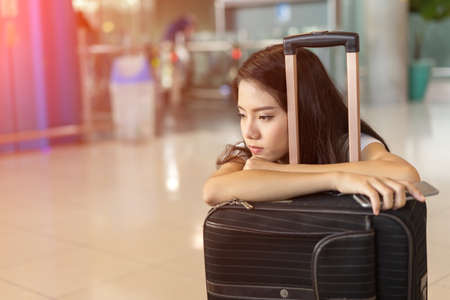 Asian woman waiting flight delay in airport hall her bored sitting wait long time early morning with baggage suitcase for travel transport Foto de archivo