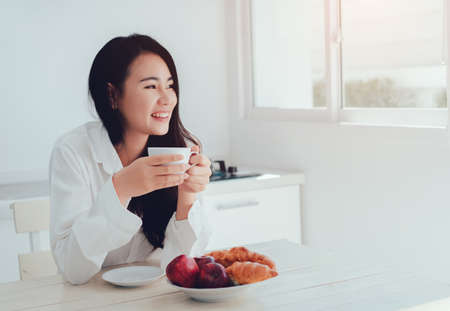 Asian woman drinking coffee in the morning and eating bread,apple fruit healthy food breakfast meal in kitchen room fresh start the day at home healthy lifestyle concept