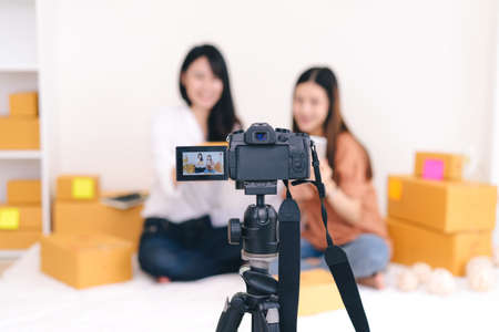 Teamwork asian women freelancer  review product working sme business at home office with parcel box for delivery online to customer by talking camera live recording video on social network Stock Photo