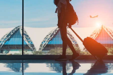 Silhouette woman travel with luggage walking side window at airport terminal international or girl teenager traveling in vacation summer relaxation holding suitcase and backpack Stock Photo