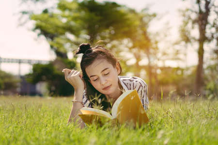 Young woman student reading book in university campus college and study learning knowledge at park outdoor Foto de archivo