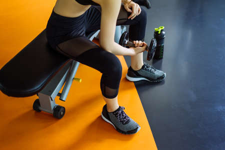 Woman young asian holding dumbbell without rack for workout exercise muscle building strong heavy weight in fitness gym and healthy lifestyle Фото со стока
