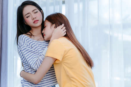 Same sex asian lesbian couple lover embrace and kiss erotic scene in the bedroom happiness feeling, LGBT sexuality female hug living together at home.