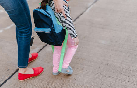 Mother and daughter pupil walking together the first day going study back to school student concept at village street with schoolbag family lifestyle. Stock Photo