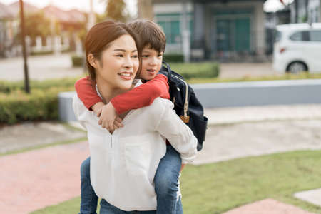 Mother get a son pupil piggyback ride from school after study school going to home with schoolbag family lifestyle. Stock Photo