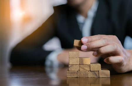 Businessman planing and strategy putting wooden blocks risk or success project hands control stack of danger tower challenge game building construction protect at office. Standard-Bild