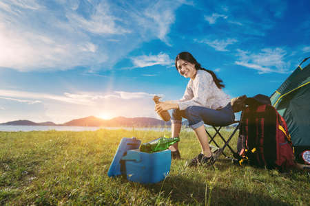 Asian woman camping and backpack travel sitting relax alone with drinks beer,water for refreshing active at morning having happy lifestyle nature mountain in forest. Stockfoto