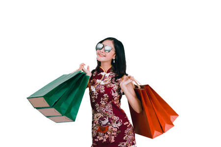 Asian woman wearing chinese dress hold shopping bag cheongsam,qipao smile in chinese new year on white isolated background Archivio Fotografico