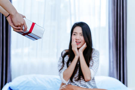 Lesbian LGBT couple surprise with Gift box give to girlfriend on bed at morning in bedroom after waking up. Stock Photo