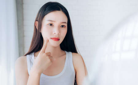 Young Asian woman squeeze acne problem face looking at mirror her without Skincare. Banco de Imagens